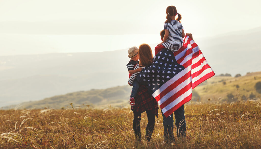 A family of 2 adults and 2 kids with a US flag